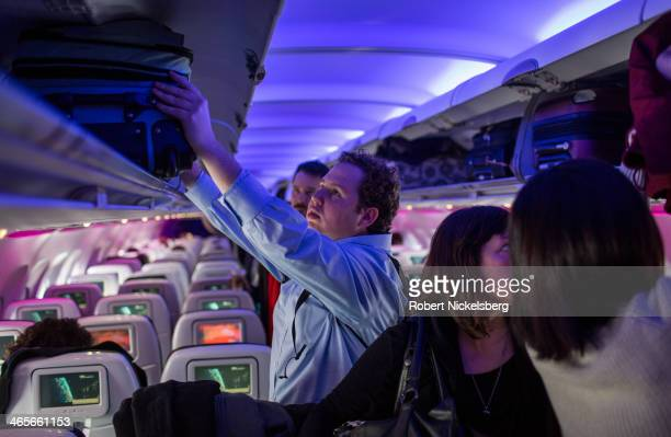 Passengers on a Virgin America flight to New York stow their bags January 12 2014 in San Francisco California