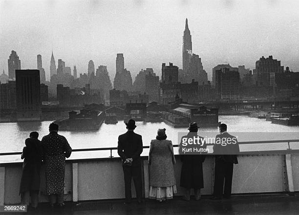 Passengers on board the Cunard White Star liner Queen Mary view the New York skyline as the ship docks in Manhattan at dawn Original Publication...