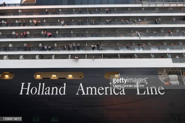 Passengers on board the Westerdam cruise ship look on in Sihanoukville on February 14 where the liner on February 13 docked after being refused entry...