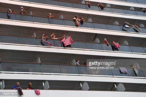 Passengers on board the Westerdam cruise ship wave traditional Cambodian krama scarves in Sihanoukville on February 14 where the liner on February 13...