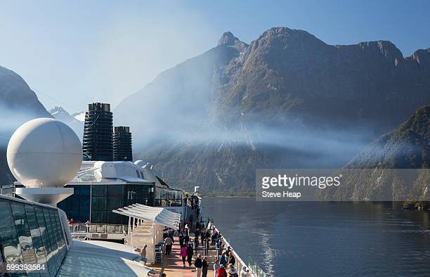 Passengers on cruise ship sailing into Milford Sound on South Island of New Zealand in early morning