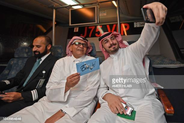 Passengers on the first Saudi Airlines direct flight from Jeddah to the Iraqi city of Arbil take a 'selfie' picture during their trip on October 1...