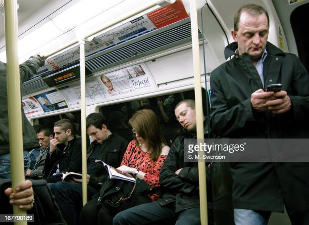 Passengers on the London Underground Northern Line during the evening commute home. One is reading, one is sleeping. One is playing on his smart...