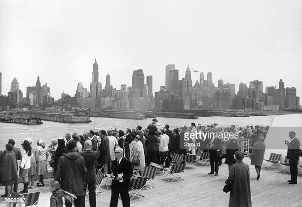 Passengers on the QE2 line the rails as the ship arrives in New York