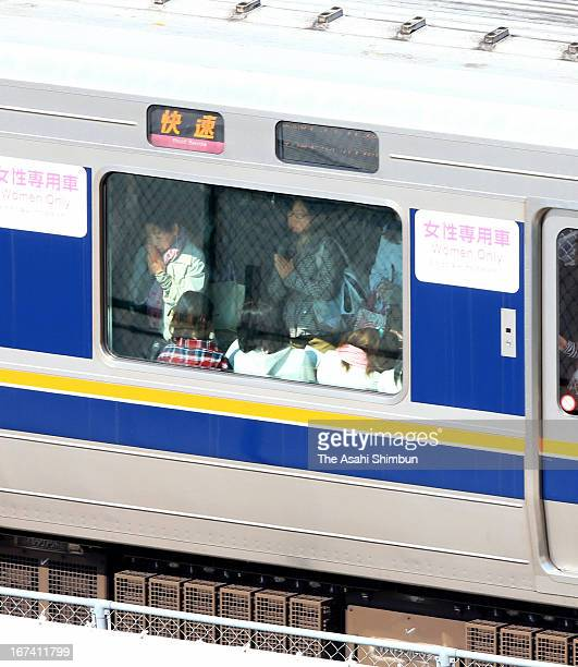 Passengers on the train observe a minute of silence while the train passes the accident site on April 25 2013 in Amagasaki Hyogo Japan 107 passengers...