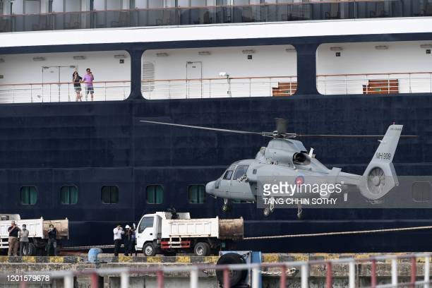 Passengers on the Westerdam cruise ship watch as a helicopter takes off in Sihanoukville on February 18 as authorities checked if any passengers that...