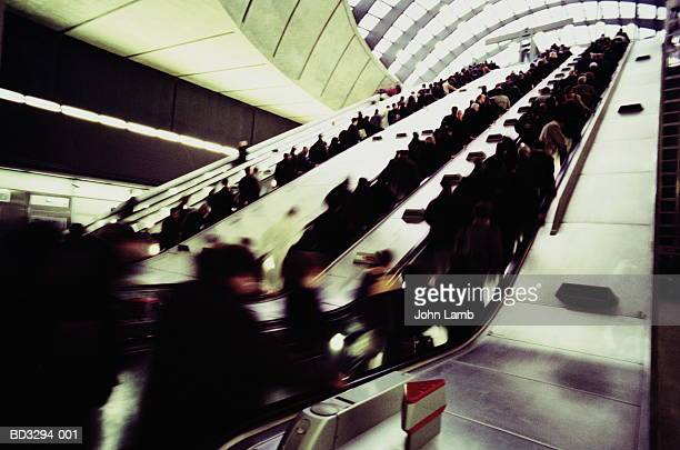 passengers on underground station escalators (blurred motion) - crowded stock pictures, royalty-free photos & images
