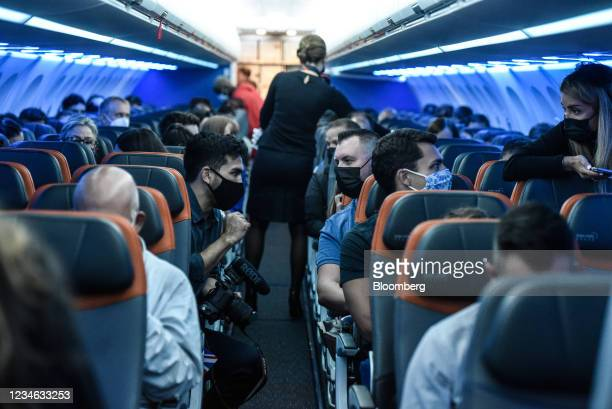Passengers onboard the JetBlue Airways Corp. Inaugural flight to London Heathrow Airport at John F. Kennedy Airport in the Queens borough of New...