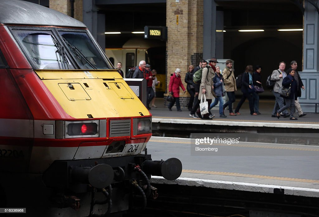 Passengers pass a pass a Virgin train as they walk along a platform at Kings Cross station, in London, U.K., on Friday, March 18, 2016. Virgin Trains will revive plans to offer high-speed Internet access on Europes busiest rail route in a bid to beat the plane and persuade business people to travel outside peak hours. Photographer: Chris Ratcliffe/Bloomberg via Getty Images