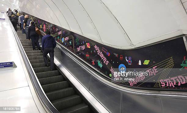 Passengers pass by a futuristic funkinspired artwork 'Transporter' created by Artist Harold Offeh and local young people for London Underground's...