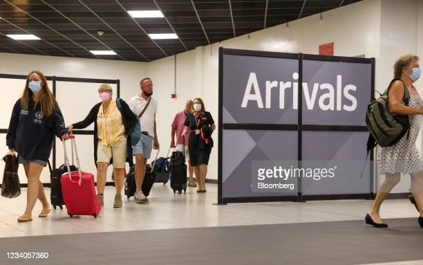 Passengers pass through the arrivals area at London Luton Airport in Luton, U.K., on Monday, July 19, 2021. While fully vaccinated tourists headed...