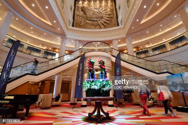 Passengers pass through the Grand Lobby of the Cunard cruise liner RMS Queen Mary 2 sailing in the Atlantic ocean during the Bridge 2017 a...