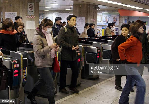 Passengers pass through turnstiles at Seibu Railway Co Ltd's Ikebukuro Station in Tokyo Monday February 21 2005