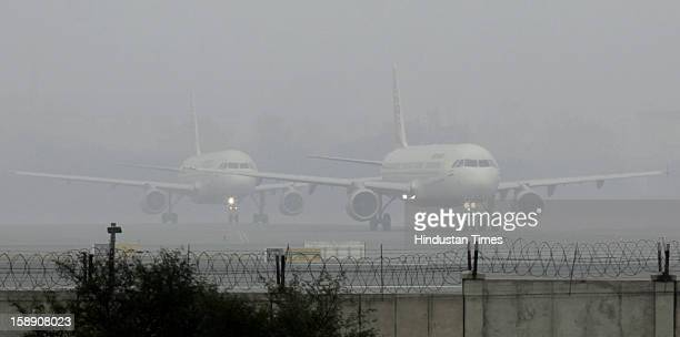 Passengers planes waits at the Runway to take off in dense fog on January 3 2013 in New Delhi India A cold wave is sweeping across north India...
