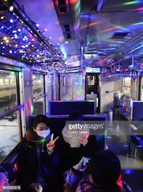 Passengers pose for a photo on Kyushu Railway Co's illuminated train in Tagawa Fukuoka Prefecture on Jan 12 2018 The Hitahikosan Line train runs in...