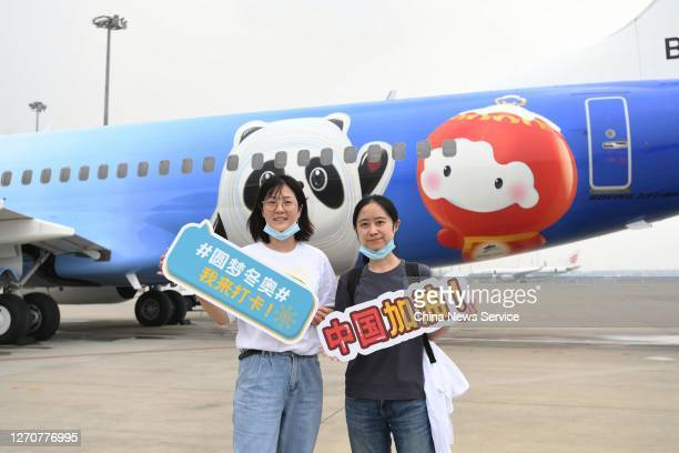 Passengers pose for photos in front of a newly painted Boeing 737 aircraft of Air China with patterns of the emblems and mascots of Beijing 2022...