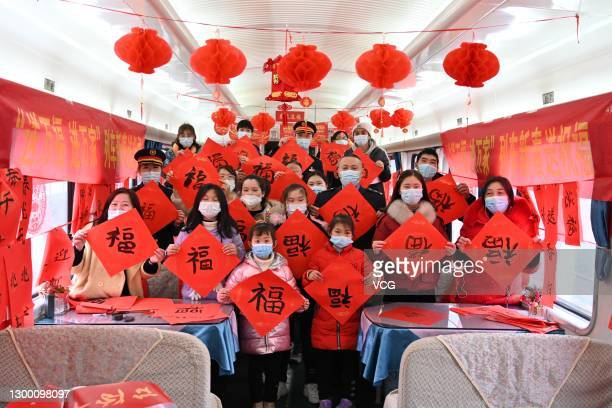 Passengers pose with Chinese character 'Fu' meaning good fortune onboard a train ahead of the Chinese New Year, the Year of the Ox, on February 3,...