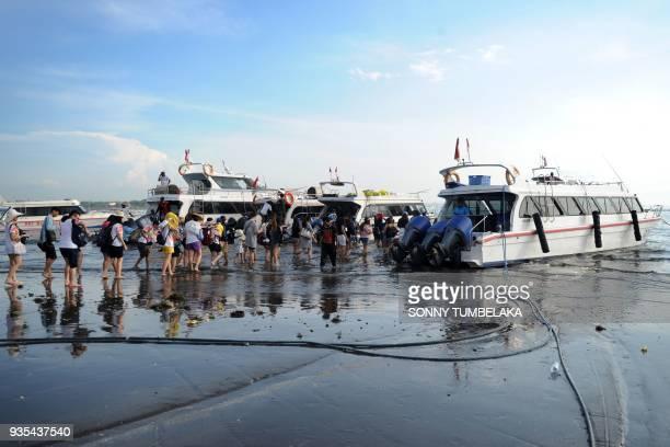 Passengers prepare to board boats to Nusa Penida island from Sanur beach on Bali on March 21, 2018. / AFP PHOTO / SONNY TUMBELAKA