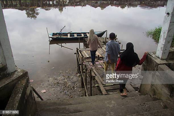 Passengers preparing to ride the boat at a simple passenger terminal on the Siak River