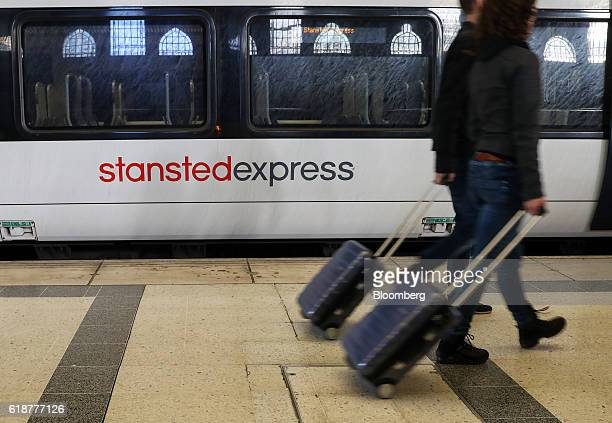 Passengers pull luggage past a Stansted Express train service serving London Stansted Airport operated by Manchester Airports Group at Liverpool...