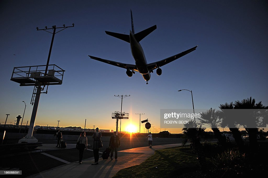 Passengers pull their luggage outside Los Angeles International Airport (LAX) as a plane comes in for a landing at dusk November 1, 2013 in Los Angeles, California. Earlier in the day a gunman opened fire with an assault rifle inside the airport, killing a security agent, creating scenes of chaos and causing widespread flight disruptions.