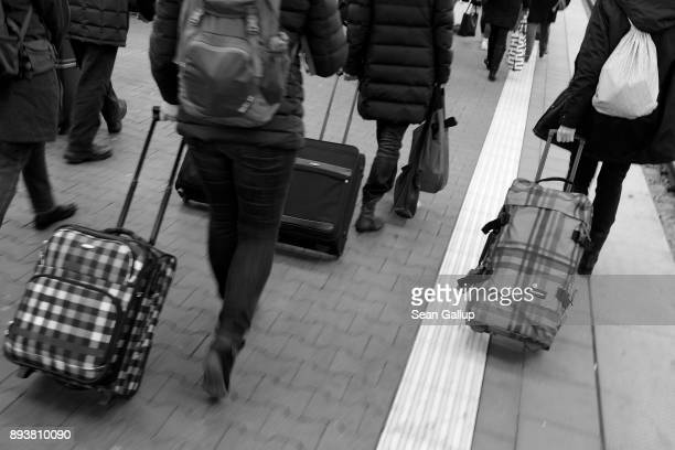 Passengers pull their suitcases on a platform after arriving on a train of German state railway carrier Deutsche Bahn at Hauptbahnhof main railway...