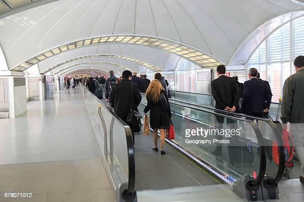 Passengers pulling luggage bags along a bright corridor Atocha railway station Madrid Spain