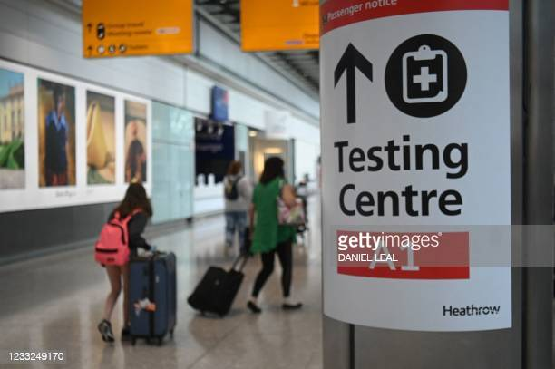 Passengers push their luggage past signage displaying the way to a Covid-19 test centre, in Terminal 5 at Heathrow airport in London, on June 3,...