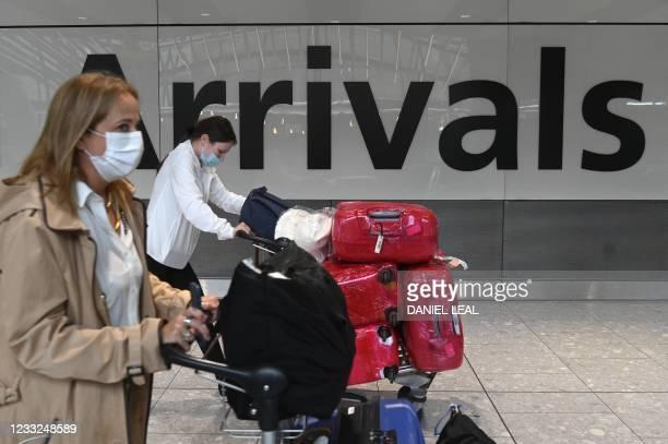 Passengers push their luggage trollies on arrival in Terminal 5 at Heathrow airport in London, on June 3, 2021. - Health Secretary Matt Hancock has...