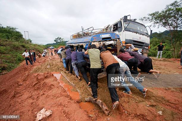 Passengers pushing a Songthaew truck stuck in mud on a bad section of the dirt road from Phonsavan to Paksan via Tathom. When a Songthaew gets stuck,...