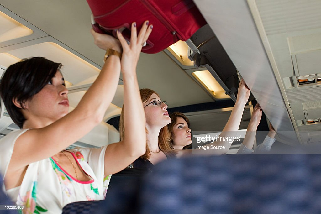 Passengers putting luggage in lockers on plane : Stock Photo