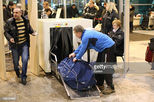 Passengers queue as they wait to pass through security scanners inside Domodedovo airport after a suspected suicide bomb attack on January 24 2011 in...