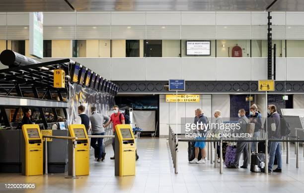 Passengers queue at a checkin desk of Schiphol airport on June 15 on the expiration day of the negative travel advice within the European Union as...
