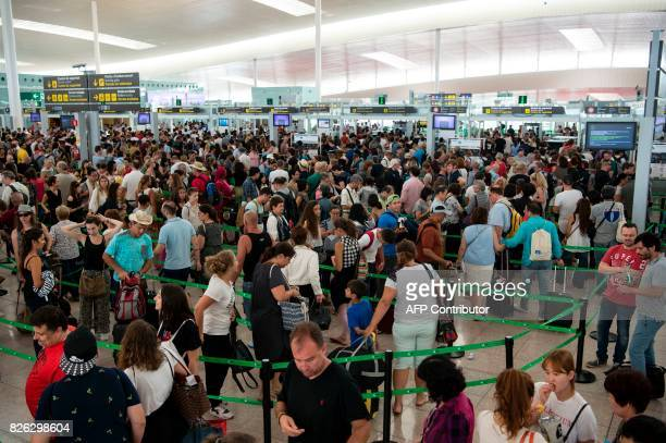 Passengers queue at Barcelona's El Prat airport as security agents strike on August 4 in Barcelona As the tourism season in Barcelona is at its peak...