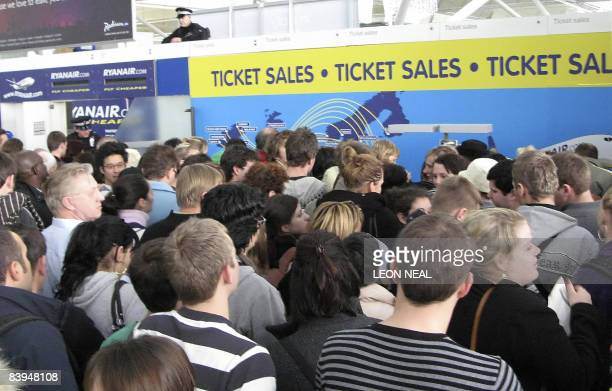 Passengers queue at budget Irish airline Ryanair's ticket sales counter at Stansted Airport December 8 following a protest by the climate action...