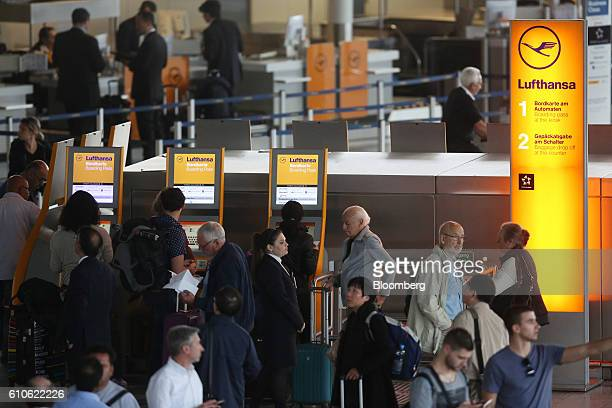 Passengers queue at selfservice ticketing machines at the Deutsche Lufthansa AG check in area inside Frankfurt Airport operated by Fraport AG in...