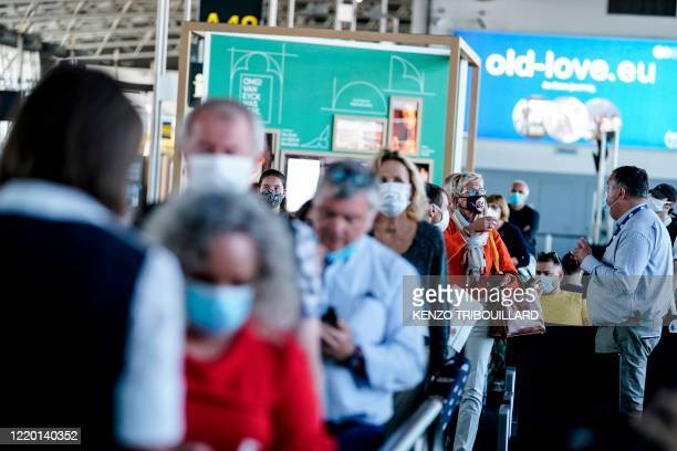 Passengers queue at the boarding gate at Brussels Airport, in Zaventem, on June 15, 2020 as Brussels Airport reopens for travels within Europe and...