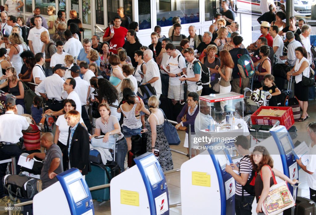 Passengers queue before checking in at Gillot airport in the French Indian ocean island of Saint Denis de la Reunion on April 22, 2010. Two thousand and five hundred passengers are stuck after Air France national company didn't charter enough planes as traffic air returned to normal. Nearly seven million passengers have been affected in the world by the disruption of air traffic due to the volcano eruption in Iceland.