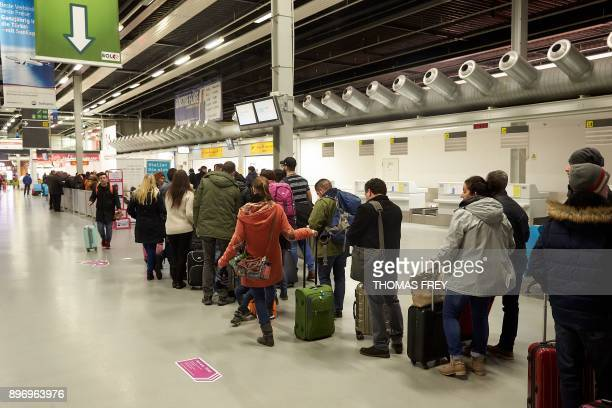 Passengers queue before checking in at the desk of the Irish lowcoast airline company Ryanair in the FrankfurtHahn Airport in Hahn western Germany on...