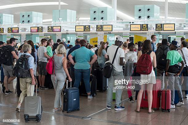 Passengers queue in front of Spanish lowcost airline Vueling checkin counters at the El Prat Airport in Barcelona on July 5 2016 Hundreds of...