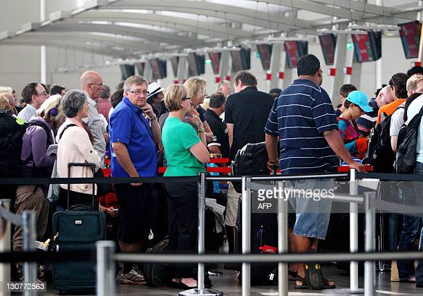 Passengers queue in the JetStar and Virgin domestic terminals at Sydney International Airport on October 30 2011 as they frantically try to book...