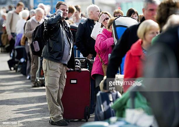 Passengers queue to board coaches for other airports after their flights were cancelled due to the volcanic ash cloud reentering the UK's airspace at...