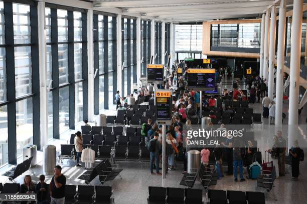 Passengers queue to board their flight at a gate in Terminal 2 at Heathrow Airport in London on July 16 2019