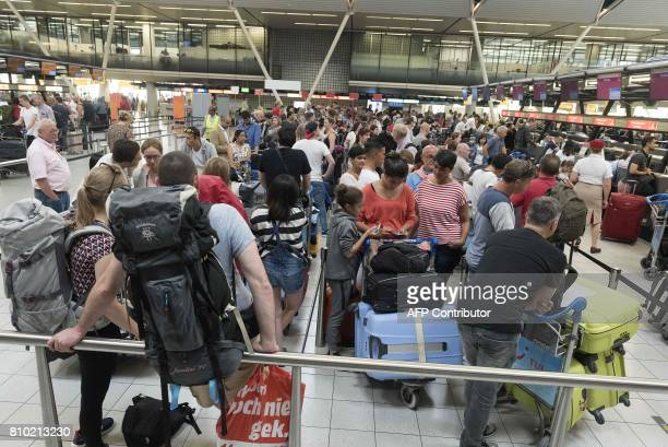 Passengers queue to checkin at Schiphol Airport in Amsterdam on July 7 on the first day of the holiday season which is traditionally the busiest time...