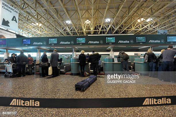 Passengers queue to checkin for an Alitalia flight at Milan's Malpensa airport on the day of the launching of the new Alitalia company on January 13...