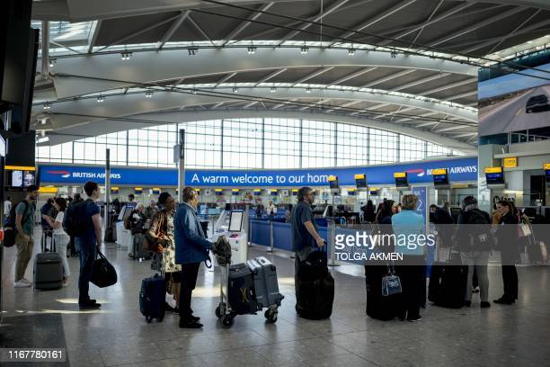 Passengers queue to checkin for their flights at Heathrow Airport's Terminal 5 in west London on September 13 2019 British Airways has cancelled all...