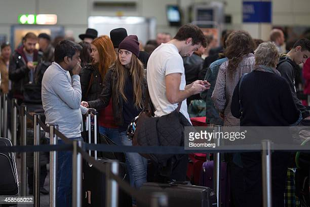 Passengers queue to drop their bags at EasyJet Plc checkin desks inside the north terminal of London Gatwick airport in Crawley UK on Thursday Nov 6...