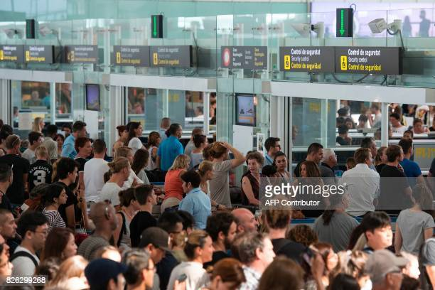 Passengers queue to pass the security control at Barcelona's El Prat airport as security agents strike on August 4 in Barcelona As the tourism season...