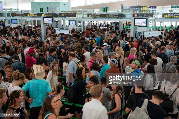 Passengers queue to pass the security controls at Barcelona's El Prat airport as security agents strike on August 4 in Barcelona As the tourism...