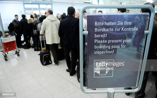 Passengers queue up at the international airport of the southern German town of Munich on January 20 2010 after parts of Munich airport were sealed...